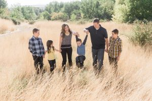 family walking through grass holding hands