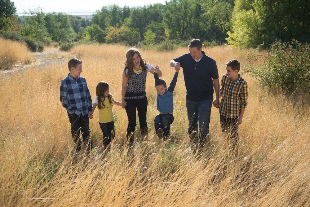 family walking through grass holding hands dark