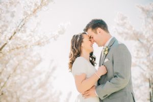 bride and groom snuggling close cherry blossoms