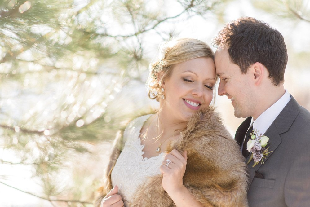 bride and groom snuggling pine tree