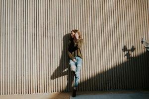 girl leaning wall hard light