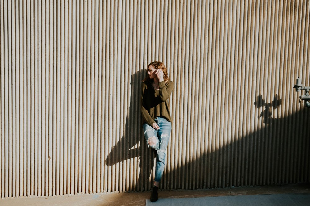 girl leaning wall hard light