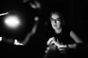 girl sitting in dark hard light
