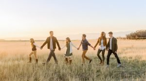 family holding hands walking in field