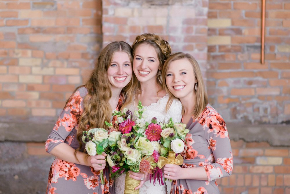 bride and bridesmaid brick wall