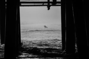surfer framed by pier in photography