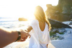 couple on beach with sun flare