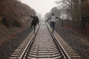 two people walking on railroad tracks