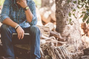 man reading in forest sitting on tree