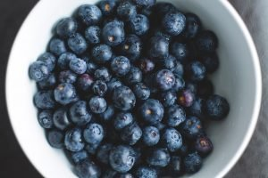 freshly picked blueberries in white bowl