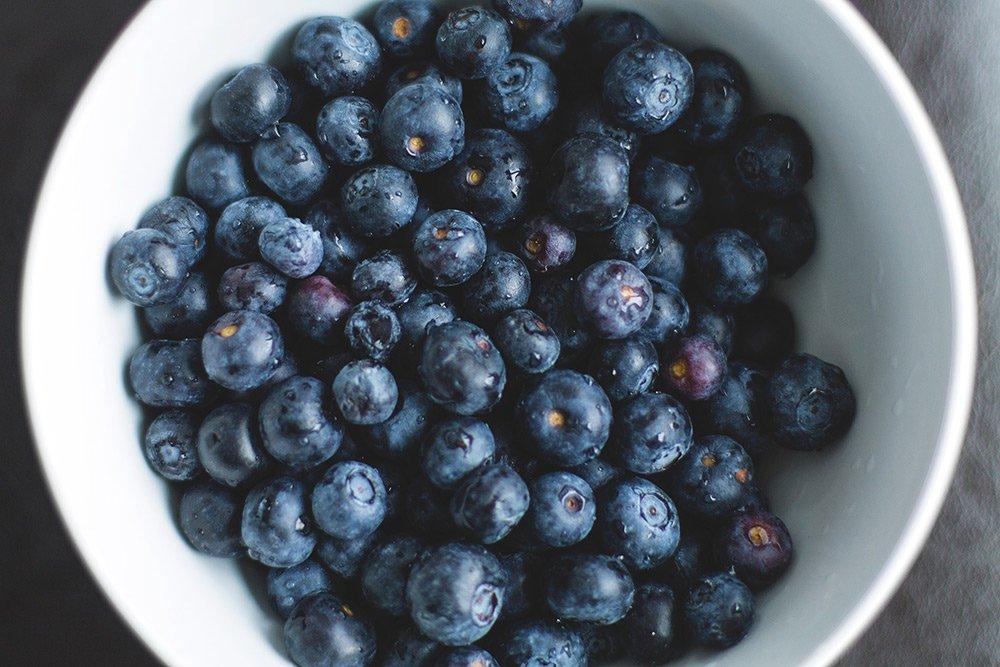 freshly picked blueberries in white bowl