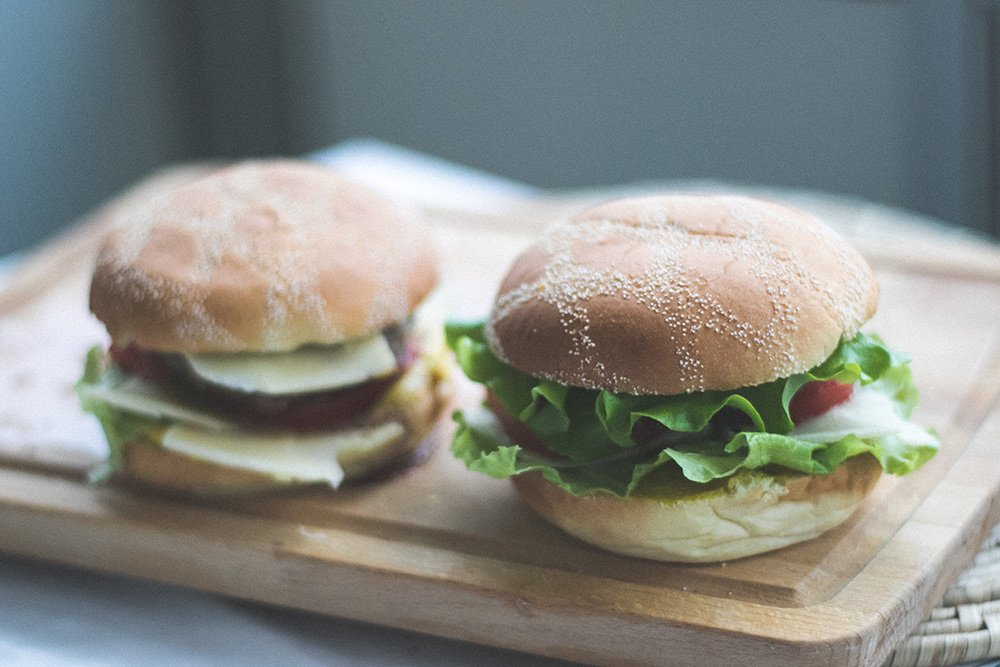turkey sandwiches on buns sitting on a cutting board