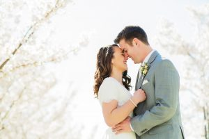 wedding couple snuggling together with cherry blossoms in the background