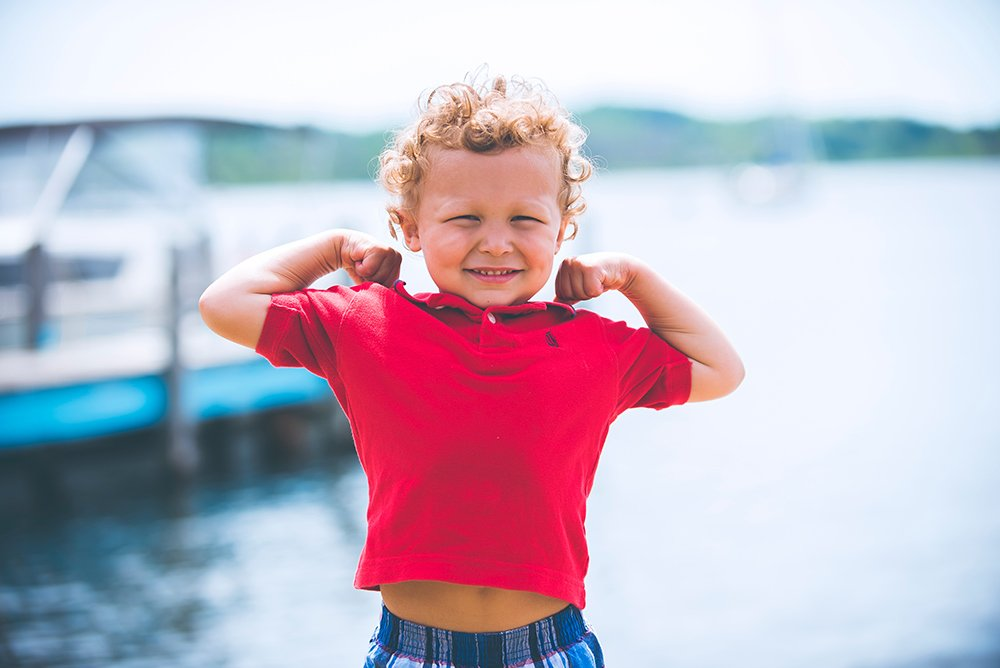 little boy in a red shirt flexing muscles while standing on a dock