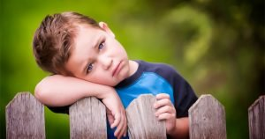 little boy laying head on arm on fence while looking sad
