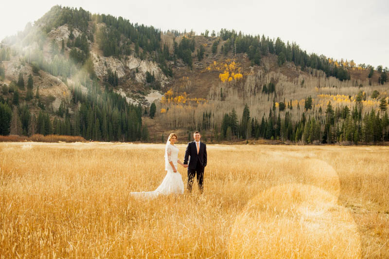 image of bride and groom walking through field with sun flare