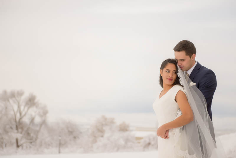bride and groom snuggling in snow