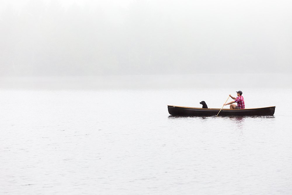 a man and his dog in a canoe on a lake