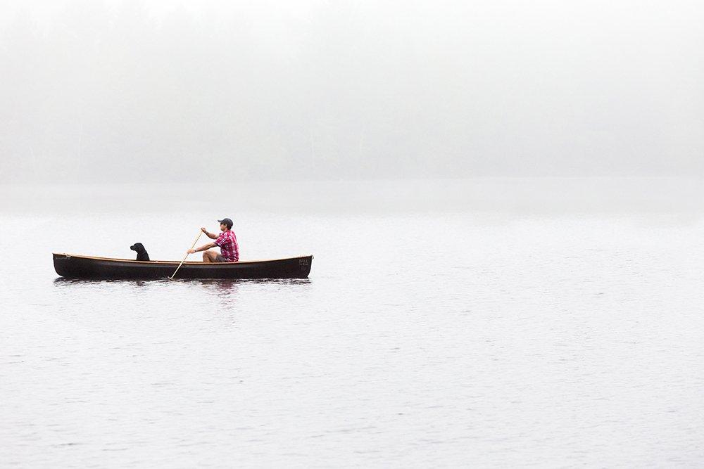 một người đàn ông và con chó của mình trên ca nô trên hồ