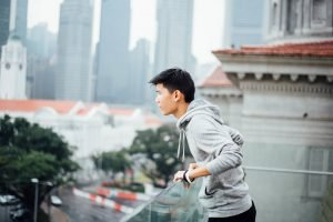 a young man on a balcony looking out into the city of Hong Kong
