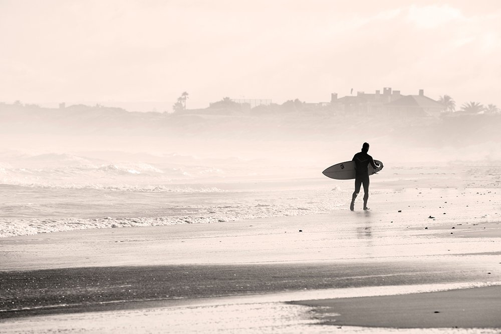 a surfer walking along the beach on the right side of the image demonstrating the rule of space in photography