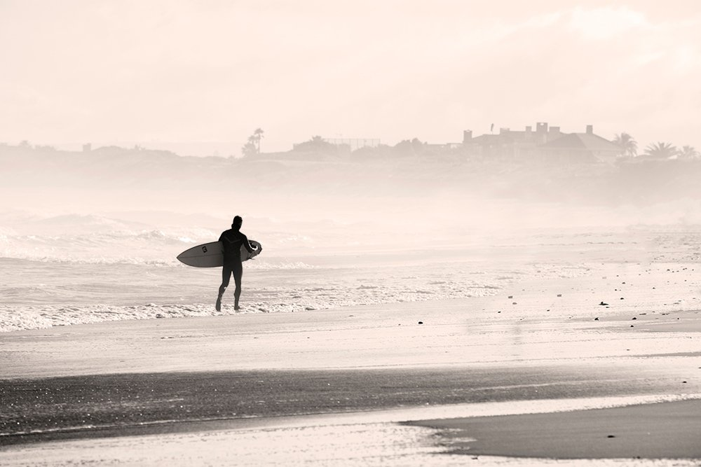 a surfer walking along the beach on the left of the frame to demonstrate the rule of space in photography