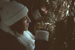 a girl wearing a snow coat and hat peering through some bushes