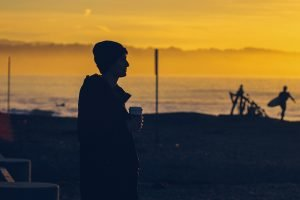 a young man holding a cup of coffee on the beach at sunset demonstrating the rule of space in photography