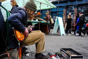 a street musician playing his guitar on a street corner in England showing the rule of space in photography