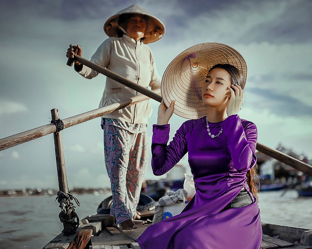 an asian woman sitting on a gondola holding her hat with a gondolier standing behind her