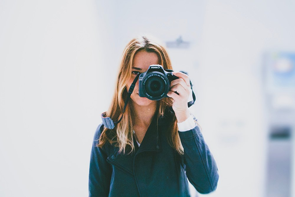 a girl with a camera to her eye taking a picture of herself in a reflection