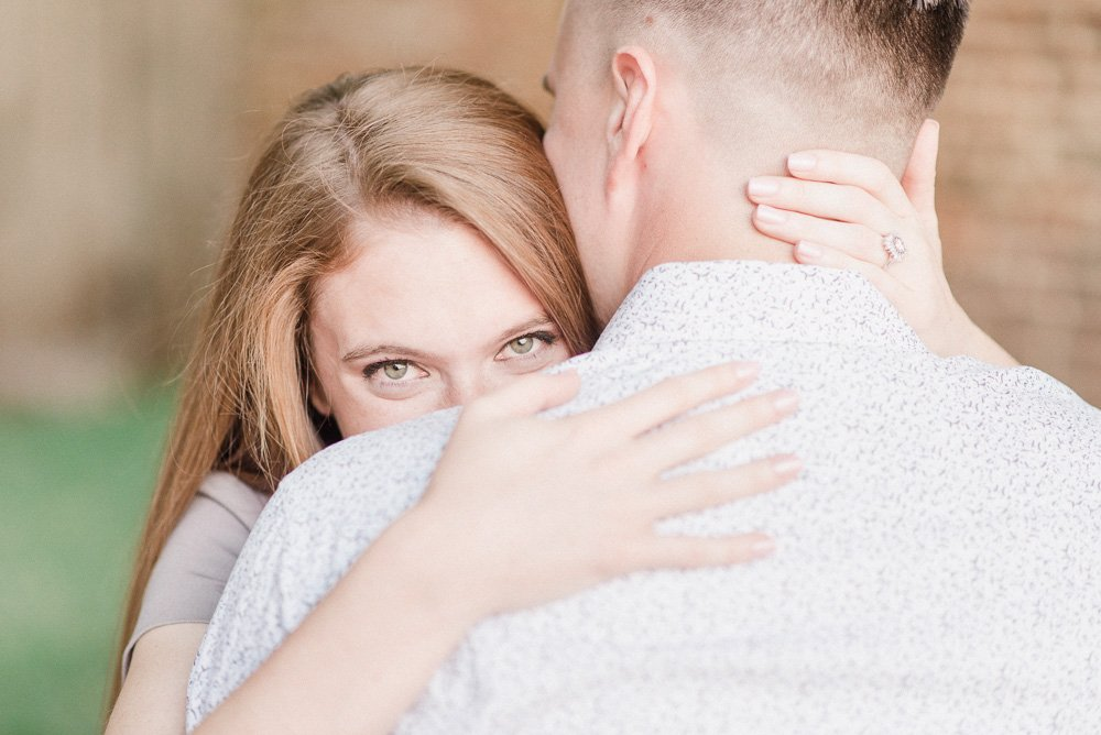 an engagement image of a girl snuggling looking over her grooms shoulder over exposed one stop of light