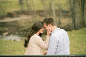 image of a couple snuggling on a bench. the girl has her hand on his face