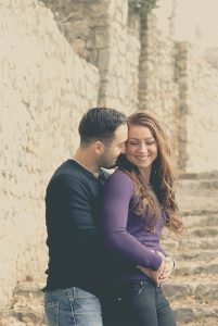 image of a couple snuggling her back to his with his arms around her