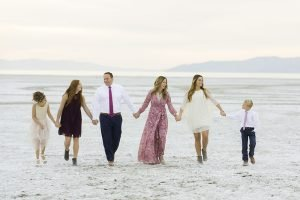 A family walking together holding hands on a beach.