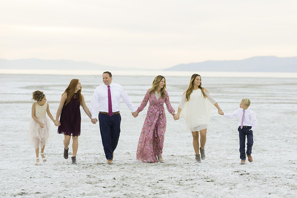 A family walking together holding hands on a beach shot with a Sigma Art 135mm 1.8 prime lens.