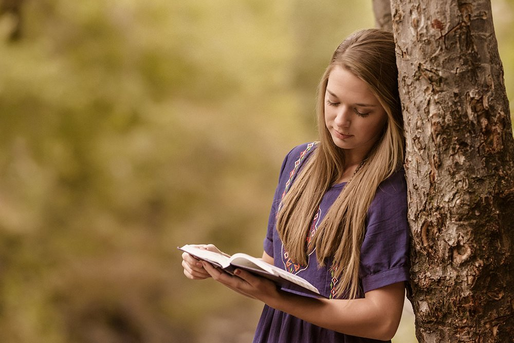 A girl leaning on a tree reading shot with a Sigma Art 135mm 1.8 prime lens.