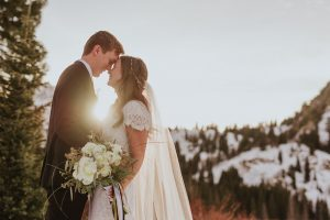 A couple touching foreheads in the snowy mountains with sun flare shot with a prime lens.
