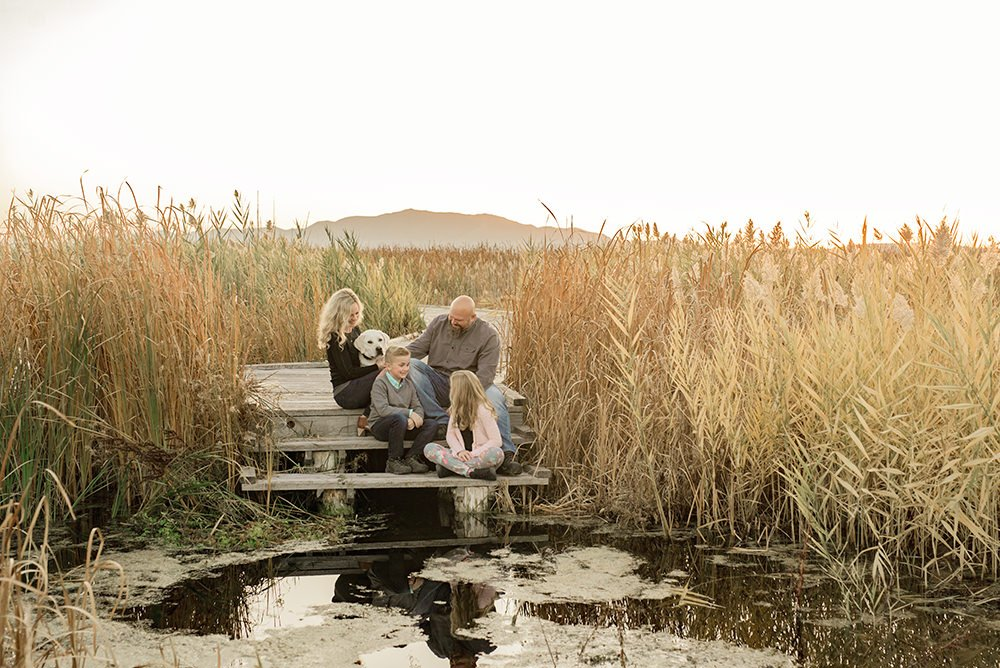 A family sitting on the dock laughing together shot with a prime lens.
