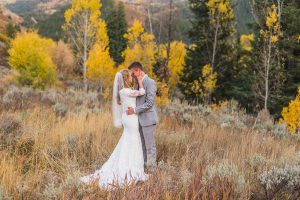 Bride and groom snuggling in the mountains in the fall shot with a prime lens.