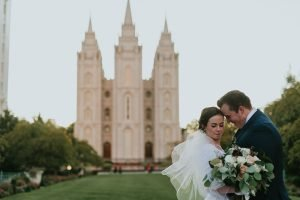 A couple snuggling in front of the Salt Lake Temple shot with a prime lens.