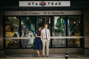 A couple standing on a train platform snuggling shot with a prime lens.