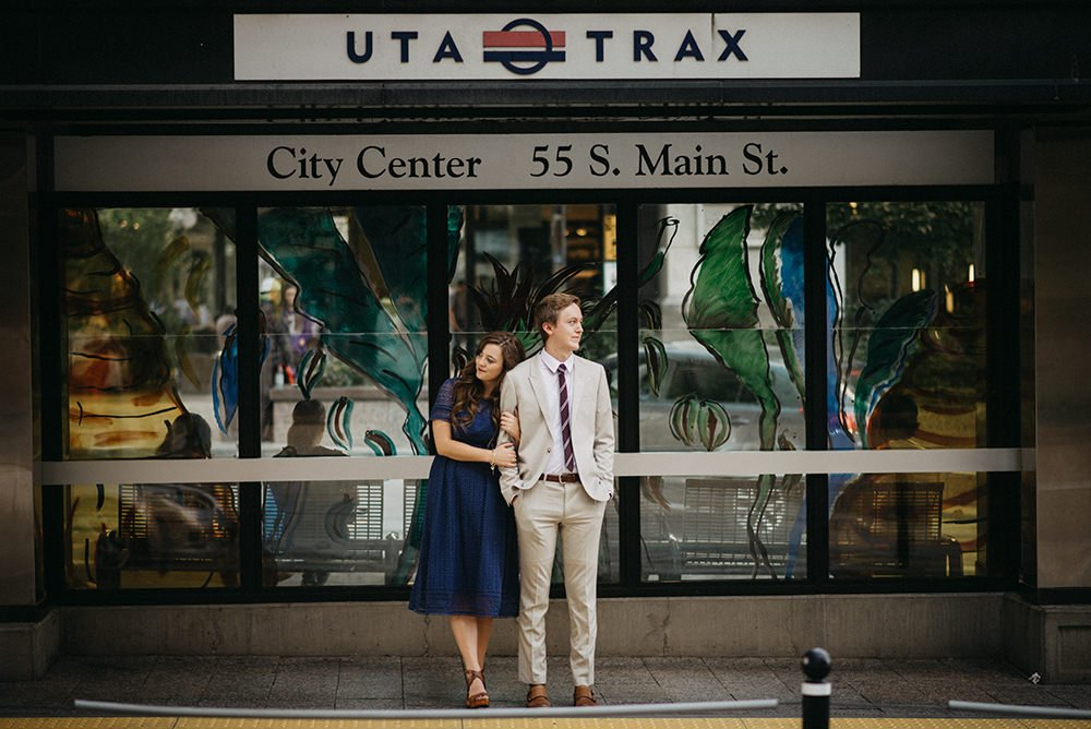 A couple standing on a train platform snuggling shot with a Nikon 85mm 1.8 prime lens.