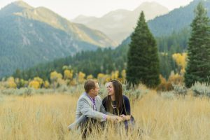 An engagement shot where the couple is sitting in a field laughing with mountains behind.
