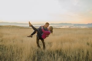Engagement shot of a guy picking up and dipping a girl in a wheat field.