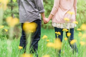 An engagement image of a couple holding hands showing just hands and legs in flowers.