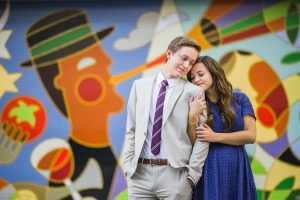 An engagement image of a couple snuggling in front of a mural.