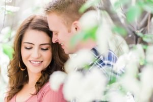A engagement image with the couple snuggling with leaves in the foreground.