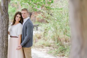 An engagement image of a couple looking at the camera while standing by a tree.